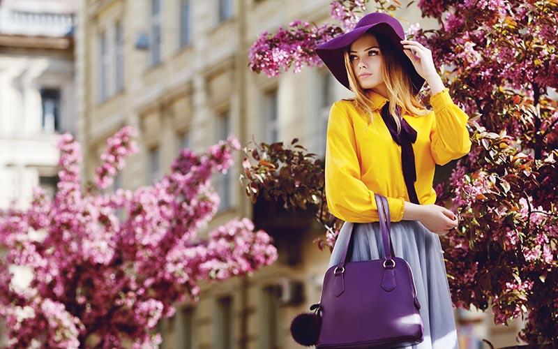 dziewczyna w kapeluszu z fioletową torebką Co ubrać w upalne dni