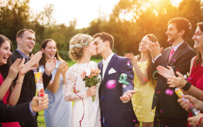 para młoda całująca się na weselu z gości w około