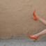 kobieta leżąca z nogami na tle ściany